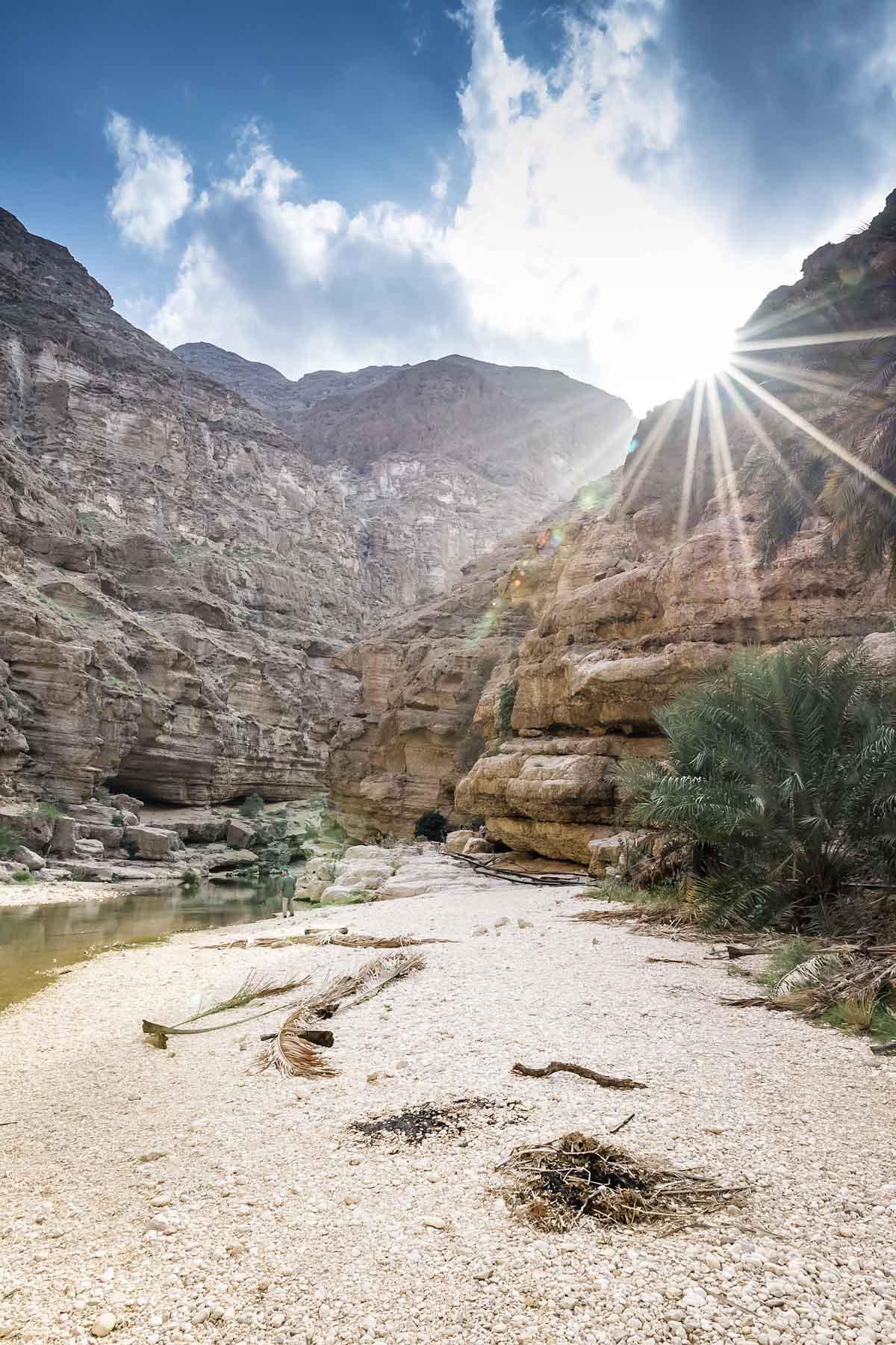 Sun Peaking through the mountains at Wadi Shab Oman - The Travel Escape